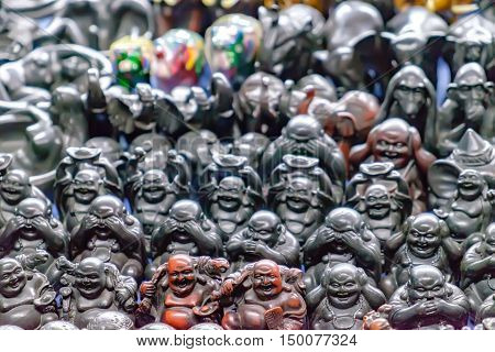 Various Thai souvenirs for sale at night market Rambuttri Alley Bangkok Thailand. Funny laughing and cheerful Buddha or Hotei. Concept of fortune prosperity and Chinese God of Wealth. Soft focus