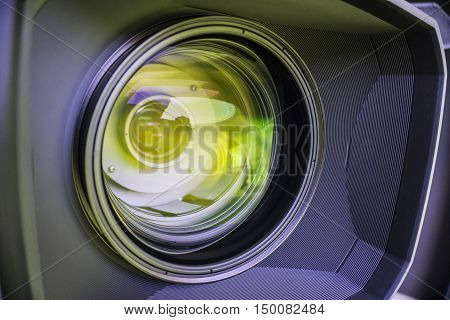 A closeup view of the glass elements in a camera lens. Objective in green light. Tilt-shift lens use.