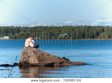 Vyborg, Russia September 03, 2016:Young couple sitting on a rock on the lake  in Vyborg, Russia
