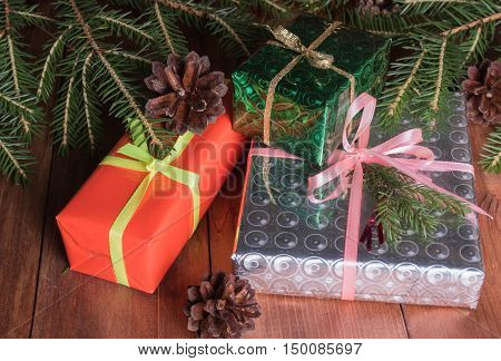 Gifts and Christmas balls lying under Christmas tree branches