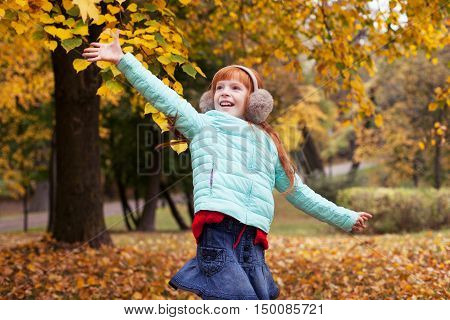 Little red-haired girl having fun in the autumn park