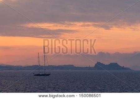 A boat sailing near Corfu island in evening light with a Corfu Old Fortress on background