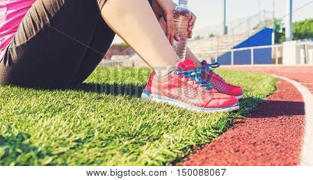 Female Jogger Sitting On The Side Of A Stadium Track