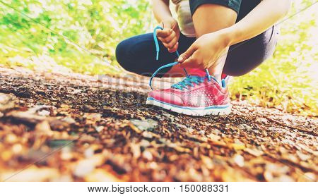 Female Jogger Tying Her Shoes In The Woods
