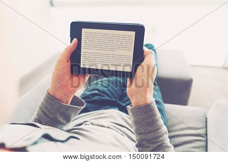 Man Reading A Book On E-reader