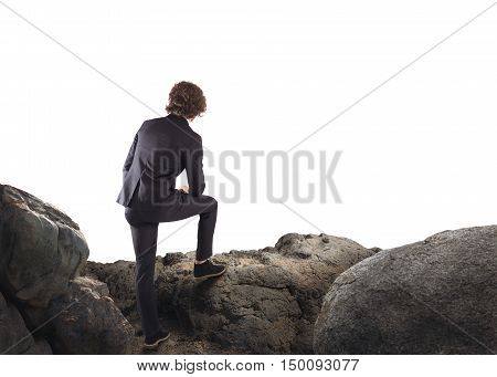 Businessman leaning on a rock watching the horizon