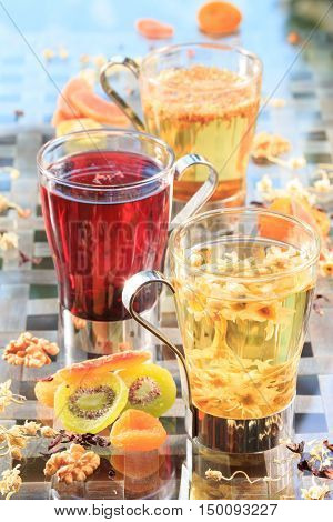 Concept of herbal tea. Variety of herbal teas in glass mugs. Healthy caffein-free drinks with dried fruits. Chamomile hibiscus and linden teas. Light airy caption. Grey background. Vertical
