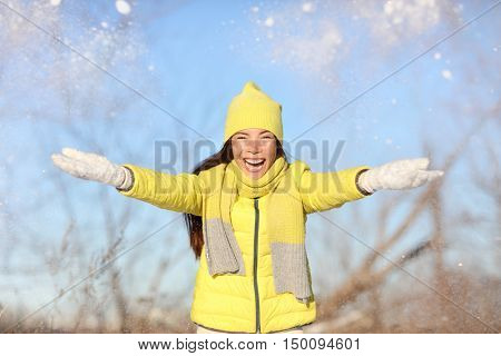 Winter fun girl throwing snow playing outside. Happy Asian woman with arms up in the air playful on a sunny day in wintertime wearing warm hat, scarf and gloves yellow outerwear.