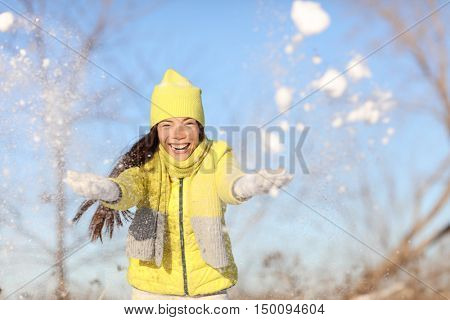 Winter fun girl playful throwing snow at camera outside. Happy Asian woman with arms up in the air playful on a sunny day in wintertime wearing warm hat, scarf and gloves yellow outerwear.