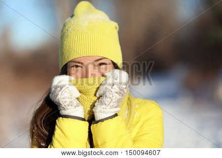 Winter freezing woman covering face from cold. Skincare concept. Cute Asian girl happy holding scarf with gloves over nose and mouth to protect from the frost. Warm outerwear for wintertime season.