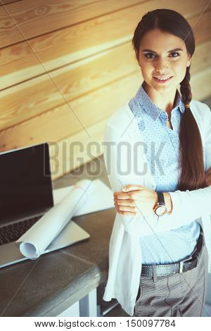 Young female standing near desk