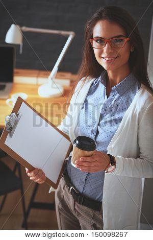 Young woman standing near desk with laptop holding folder and cup of coffee
