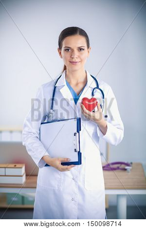 Young woman doctor holding folder and  a red heart, isolated on white background