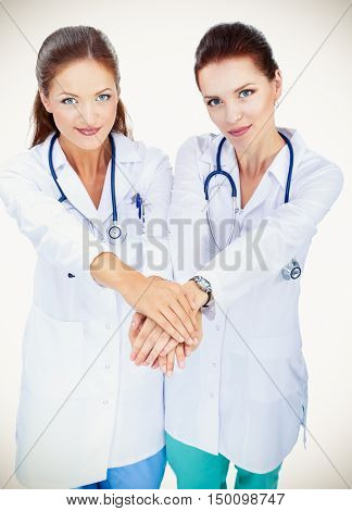 Yomg woman doctor stacking hands together over white background