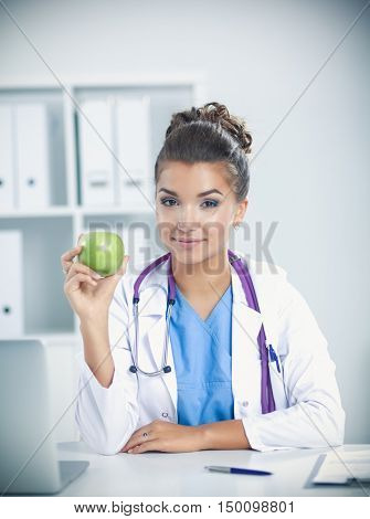 Female doctor hand holding a green apple, sitting