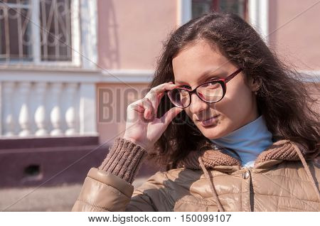 Girl in a jacket shows the glasses
