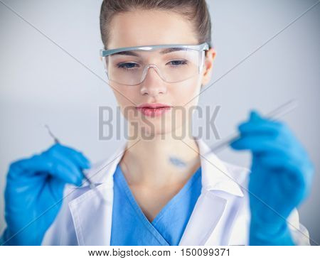 Attractive female dentist with tools , standing on gay background