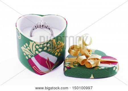 A beautiful diamond ring sit in a heart-shaped Christmas box.  On a white background.