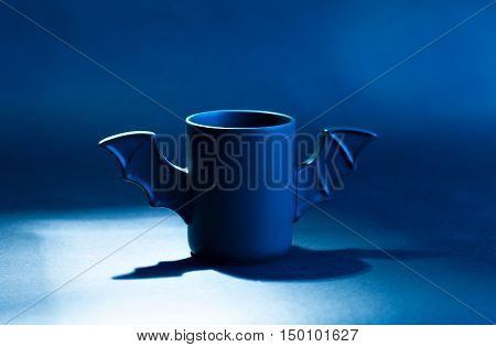 A cup of coffee as a bat for Halloween on black background. Blue light and shadow. Toy bat. Halloween concept