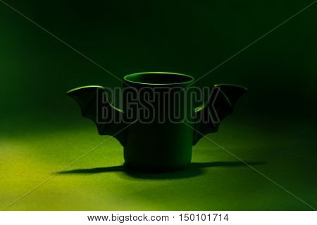 A cup of coffee as a bat for Halloween on black background. Green light and shadow. Toy bat. Halloween concept