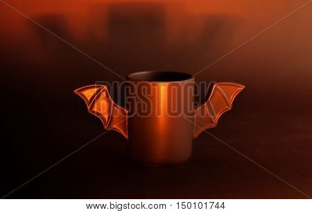 A cup of coffee as a bat for Halloween on black background. Red light and shadow. Toy bat. Halloween concept