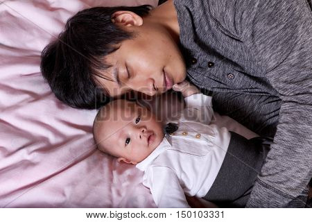 Father falls asleep before his infant baby boy while lying on the bed