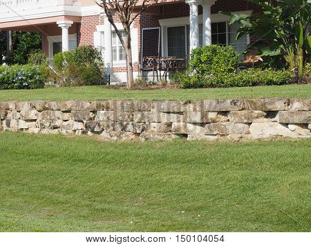 small retaining wall made of pavers by a grass area