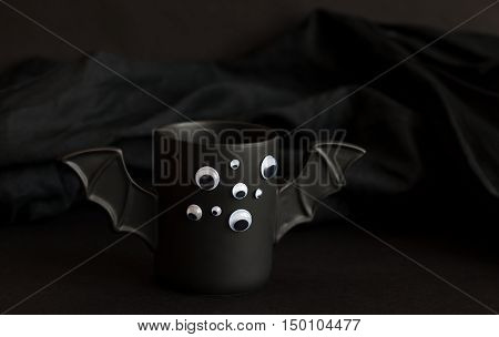 A cup of coffee as a bat for Halloween with eyes on a black background. Green light and shadow. Toy bat. Halloween concept