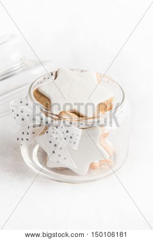 Close up of a glass jar full with christmas homemade star cookies over white fluffy background.
