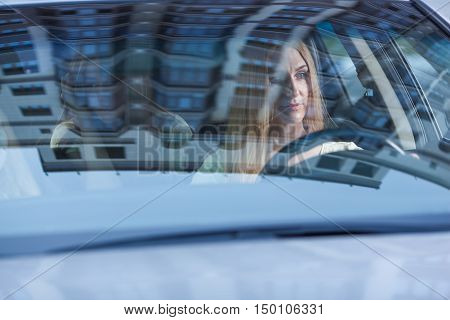 blonde beautiful woman with driving a car. Her cute daughter sitting on rear. View from behind the glass.