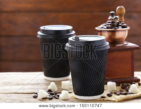 paper cup with hot coffee and coffee beans