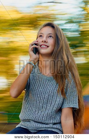 girl having fun on spinning roundabout and using a mobile phone. Autumn. Naturally blur motion