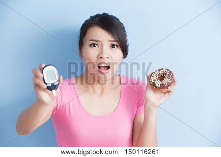 Woman holding a blood glucose meter and donut to prevention diabetes isolated on blue background asian