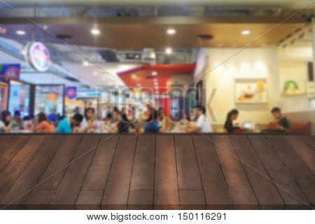 wooden table mock up interior restaurant design advertising food court with wooden table texture background empty table ready for product display montage over blurred food court background.