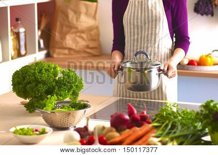 Young Woman Cooking in the kitchen. Healthy Food.