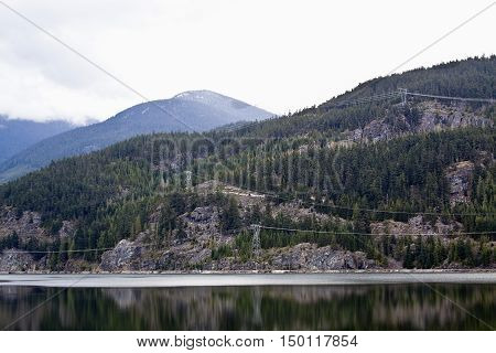 View of the power lines strung along the Rockies outside of Whistler Blackcomb BC reflections on the lake beside the Sea to Sky highway on a bright day in April with misty peaks.
