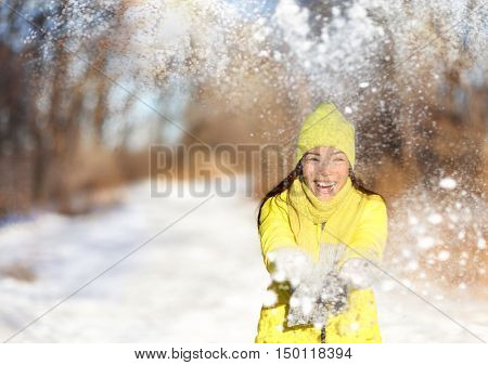 Winter snow fight happy girl throwing snow playing outside. Joyous young Asian woman having fun in nature forest park on snowy day wearing yellow outerwear with warm accessories: gloves, hat, scarf.