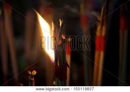 Blaze joss sticks embroidered into a pot of worship.