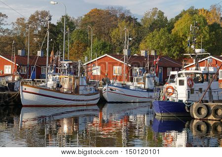 Small fishing boats in the harbor reflecting in the water a perfect sunny windless morning