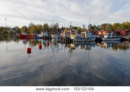 Small fishing boats in the harbor reflecting in the water a perfect sunny windless morning in October 02 2016 in Grisslehamn Stockholm Sweden