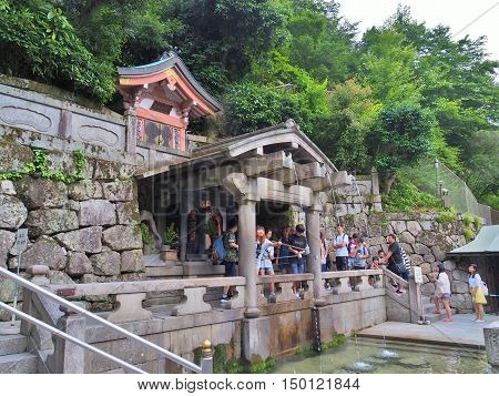 KYOTO, JAPAN - JUNE 08, 2016: Many people collecting water from the Otowa-no-taki waterfall at Kiyomizu-dera temple. Visitors believe that water have enhance health, longevity, and success in studies.