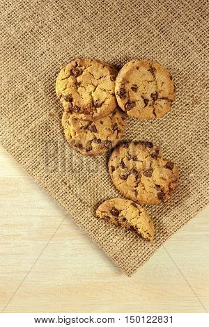 A photo of chocolate chips cookies, shot on a burlap and light wooden background texture, with copyspace