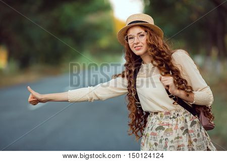 Hitchhiking tourism concept. Portrait of travel hitchhiker woman with hat and backpack walking on road during holiday travel