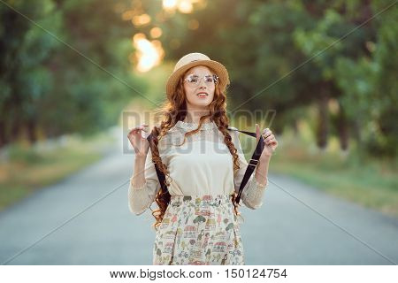 Young girl traveler enjoy the travel on foot. Portrait of happy woman walking with hat and backpack on the road. Adventure is coming concept