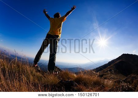 Concept: freedom. A man standing at mountain top with open arms set against a beautiful sunset.