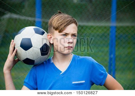 Portrait of a boy with a ball playing football