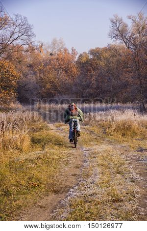 Winding Forest Road And Cyclist Woman Riding A Mountain Bike