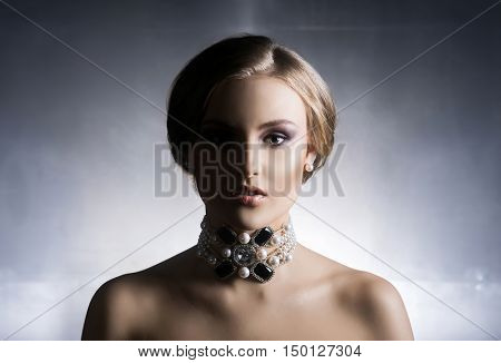 Portrait of young, beautiful and rich woman in shiny jewels. Metal background