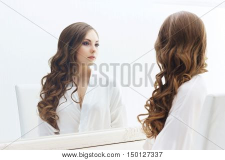 Young and beautiful girl preparing makeup. Bride doing make-up near the mirror.  Cosmetics and skin care concept.