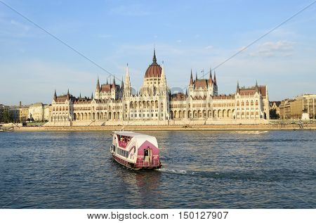 BUDAPEST, AUGUST 9: Tourists enjoying the beautiful weather visit the Parliament on August 9, 2015 in Budapest, Hungary. The Parliament, built in Neo-Gothic style and located on the bank of Danube.